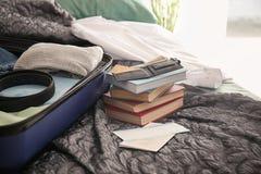 Geldbörse, Dokumente und offener Koffer mit verpackten Sachen auf Bett stockbild