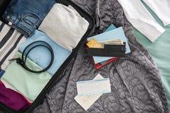Geldbörse, Dokumente und offener Koffer mit verpackten Sachen auf Bett, Draufsicht stockfoto