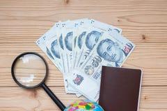 Geldbanknote mit Pass, Lupe, Kugel auf Holztisch, Draufsicht und Kopienraum Zeit, in Singapur zu reisen stockbild