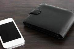 Geldbeutel und Telefon auf h?lzernem Hintergrund lizenzfreie stockbilder