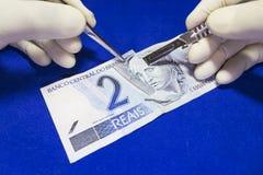 Geldchirurgie - brasilianische reais Stockfotos