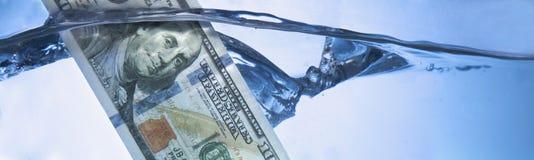 Geldconcept die Amerikaanse dollar tonen die in water als symbool dalen van stock afbeeldingen