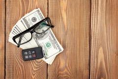 Geldcontant geld, glazen en auto verre sleutel op houten lijst Stock Foto's