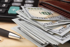 Gelddollars, beurs, pen en calculator op een houten lijst Close-up Stock Afbeeldingen