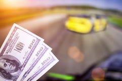 Gelddollars op de achtergrond van een TV waarop afwijking op auto's toon, sporten die, gelddollars wedden royalty-vrije stock fotografie