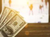 Gelddollars op de achtergrond van een TV waarop biathlon toont, sporten weddend, biathlon en dollars royalty-vrije stock foto's