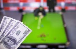 Gelddollars op de achtergrond van een TV waarop een spel van snooker toon, sporten die, dollars wedden stock afbeeldingen