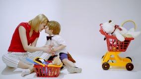 Geldeinsparung Wie man reiches gefälschtes Buch erhält Mutter und Sohn fügen Münzen zum Sparschwein zusammen mit völlig Glückmome stock video footage
