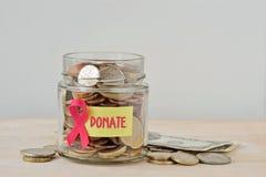 Geldglas voll Münzen mit rosa Band und Aufkleber spenden - Brustkrebsnächstenliebe und Forschungsfondkonzept lizenzfreie stockfotografie