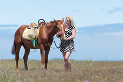 Gelding and blonde woman. Young blonde woman in polka-dot dress with brown horse Stock Photos