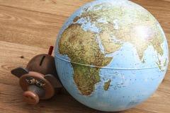 Geldkasten mit Kugel der Welt Lizenzfreies Stockbild