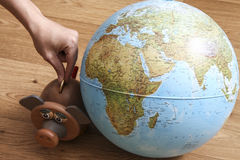 Geldkasten mit Kugel der Welt Stockbild