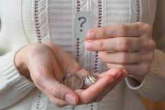 Geldmünze in der Hand und ein Fragezeichen Lizenzfreie Stockfotos