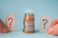 Geldmünze in der Hand und ein Fragezeichen Stockfoto