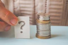 Geldmünze in der Hand und ein Fragezeichen Stockfotos