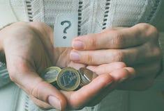 Geldmünze in der Hand und ein Fragezeichen Lizenzfreies Stockfoto