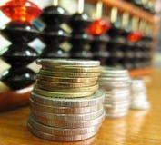 Geldmünze mit Abakus Lizenzfreie Stockfotos