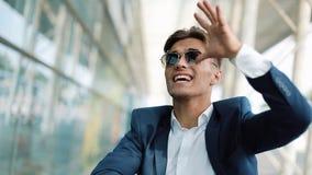 Geldregen fällt vom Himmel, ein Fanggeld des jungen Mannes Ein Geschäftsmann verliert Geld Geschäft, Leute und Finanzen stock video footage