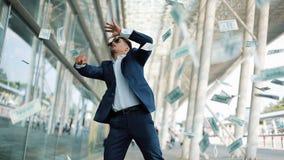 Geldregen fällt vom Himmel, ein Fanggeld des jungen Mannes Ein Geschäftsmann verliert Geld Geschäft, Leute und Finanzen stock video
