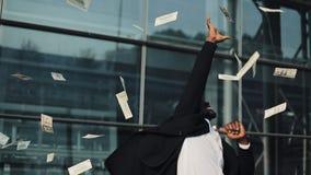 Geldregenfälle vom Himmel, fängt ein glücklicher Mann des jungen Afroamerikaners Geld Geschäft, Leute und Finanzkonzept stock footage