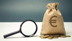 Geldtasche mit Eurozeichen und Lupe Das Konzept des Findens von Quellen der Investition und der Sponsoren Barmherzige Kapitalien stockbild