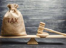 Geldzak met de van de woordbelasting en hamer rechter op de schalen Het concept het betalen van belastingen en schuldaflossing Re stock afbeelding