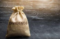 Geldzak met de woorddividenden Een dividend is een betaling door een bedrijf aan zijn aandeelhouders als distributie van winsten  stock afbeeldingen
