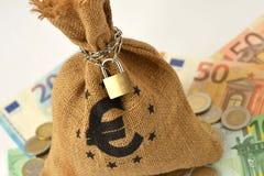 Geldzak met hangslot en ketting over euro bankbiljetten en muntstukken - stock afbeelding