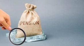 Geldzak met het het woordpensioen en meetlint Daling/verminderingspensioenbetalingen Pensionering Financierende gepensioneerden V royalty-vrije stock afbeeldingen