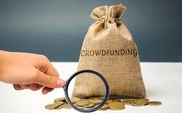 Geldzak met muntstukken met woord het crowdfunding Vrijwillige vereniging van geld of middelen via Internet Steunontvangers stock foto