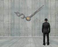 Geldzeichen-Uhrhände auf hölzerner Wand mit Gekritzeln und Mann looki Stockbilder