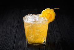 Gele alcoholcocktail met kers en citroen op zwarte achtergrond stock foto