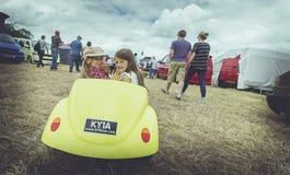 Gele auto en meisjes Royalty-vrije Stock Afbeeldingen