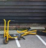 Gele autopedden in een schoolwerf Stock Foto