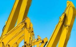 Gele backhoe met hydraulisch zuigerwapen tegen duidelijke blauwe hemel Zware machine voor uitgraving in bouwwerf hydraulisch stock foto