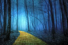 Gele Baksteenweg die door een griezelig bos leiden stock afbeelding