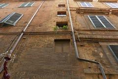 Gele bakstenen muur van het oude gebouw met downspouts Stock Foto's