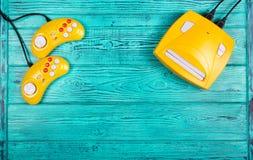 Gele bedieningshendel twee en spelconsole op een blauwe houten achtergrond Videospelletjeconsole GamePad Royalty-vrije Stock Afbeelding