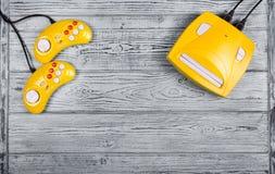 Gele bedieningshendel twee en spelconsole op een grijze houten achtergrond Videospelletjeconsole GamePad Stock Fotografie