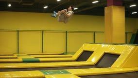 Gele behandelde trampoline voor jonge sportieve mensen Het atletische mannetje voert voorsalto mortaleshoppen van het platform ui stock videobeelden