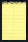 Gele besliste spiraalvormige blocnote over zwarte Royalty-vrije Stock Fotografie