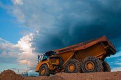 Gele Besnoeiingsvrachtwagen op de wegbouw vóór zwaar onweer Stock Afbeeldingen