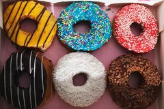 Gele, blauwe, rode, witte en bruine donuts met kleurrijk bestrooit in een doos naast elkaar stock fotografie