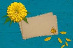 Gele bloem, bloemblaadjes en oud document op de turkooise houten raad Stock Fotografie