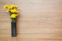 Gele bloemchrysant in vaas op hout blackground Royalty-vrije Stock Foto's
