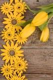 Gele bloemendecoratie op houten achtergrond Stock Afbeeldingen
