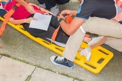 Gele brancard en patiënt voor de dienstverwonding van de noodsituatieparamedicus wordt verwond met medische apparatuur in de situ stock afbeelding