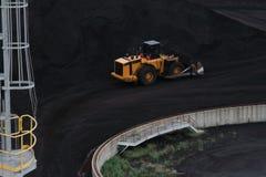 Gele Bulldozer die Zwarte Steenkool bewegen Stock Fotografie