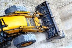 Gele bulldozer, ladend grint voor wegenbouw stock afbeeldingen