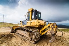Gele bulldozer op sporen stock foto